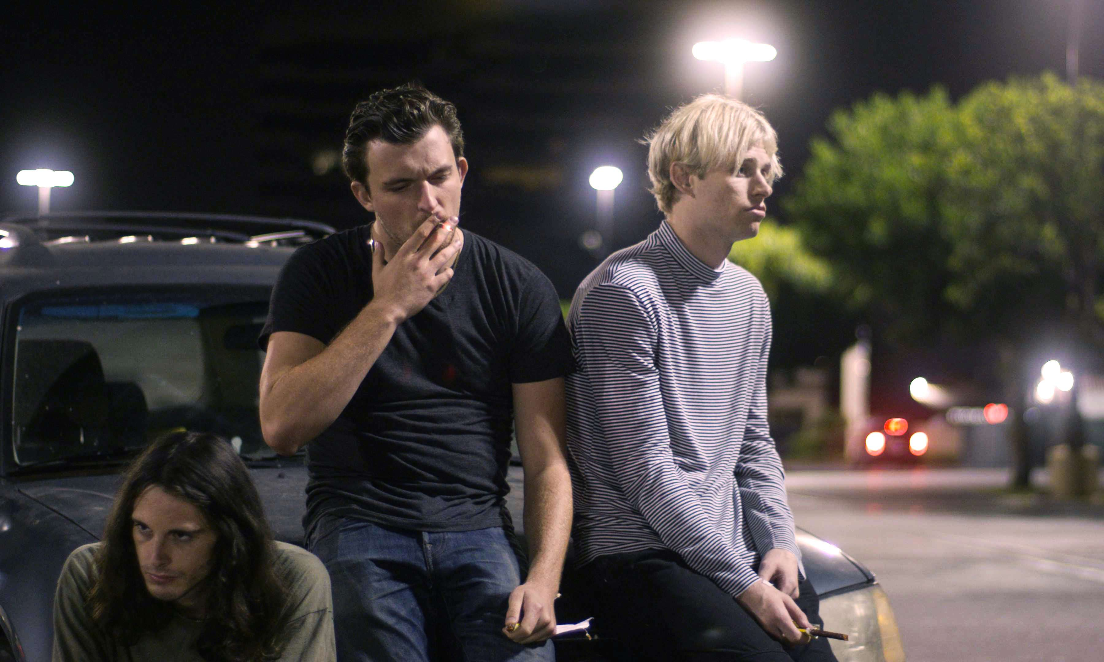 Three teenage boys sit on the hood of a car in a parking lot at night. The middle one, in a black t-shirt and jeans, is smoking, as is the blonde on the right.